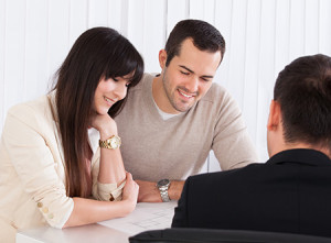 Image of a couple meeting with a man at a table.